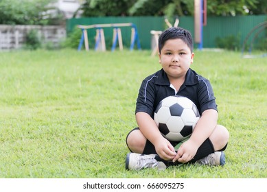 sitting obese fat boy  soccer player with football on green grass background, healthy concept