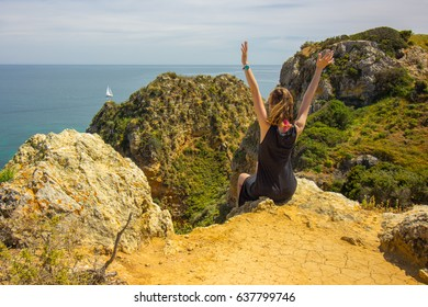 Sitting on a cliff with hands up in the air overlooking Algarve coastline