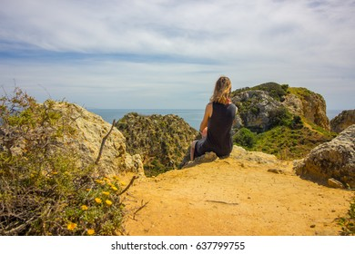 Sitting on a cliff overlooking Lagos coastline in Algarve