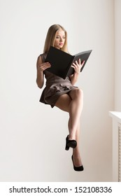 Sitting on invisible chair. Thoughtful young blond hair woman sitting on invisible chair and reading book