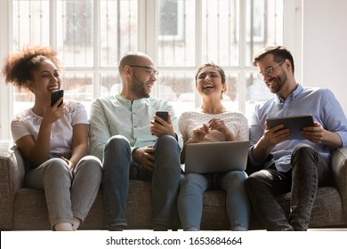 Sitting on sofa four multiracial friends using diverse devices hold phones laptop and tablet have fun together chatting enjoy live communication, generation and modern gadgets, social networks concept