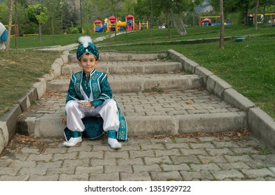 sitting on a stony ladder between the grasses, wearing the ottoman sultans on it, in blue, having a sunnah dress, having a children's park behind it, circumcision boy