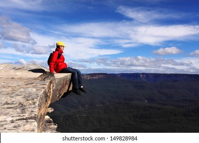 Sitting on Top of the World - hiker rests high on a cliff ledge  and admires views of Blue Mountains on a beautiful sunny day.  Selective focus.  adventure achievement risk success