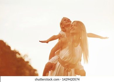 Sitting on the woman's shoulders. Mother and daughter enjoying weekend together by walking outdoors in the field. Beautiful nature.