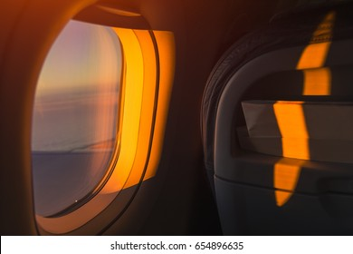 Sitting in a plane near the window with a beautiful view of the sunset and sea enjoying the moment of traveling. Tourist is ready for a amazing summer journey with his best friends.