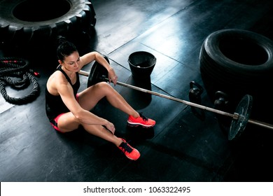 Sitting and resting on floor at crossfit gym, woman exercise hard with weigths