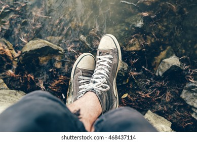 Sitting at riverbank, young adult casual male legs wearing sneakers near the flowing water