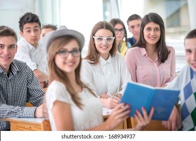 Sitting teenage pupils posing in schoolroom