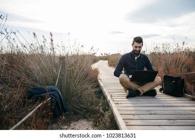 Adult man sitting on long wooden walkway in drya sunny grass and using laptop working remotely.