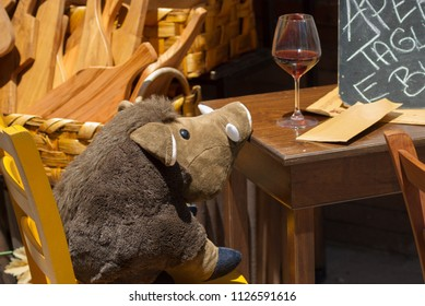 Sitting wild boar drinking wine in an Umbrian restaurant