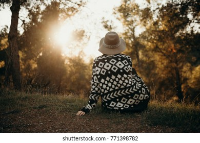Sitting woman in her back, in the middle of the forest, watching the sunset alone.