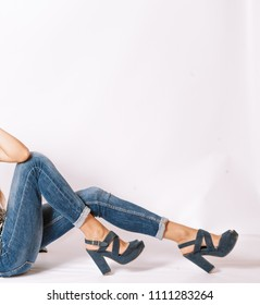 Sitting Woman Legs in skinny jeans on gray with space for text