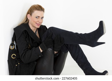 sitting woman wearing black clothes and boots with a handbag