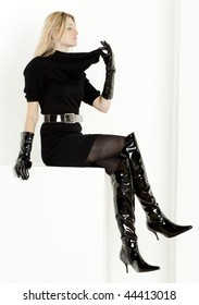 sitting woman wearing black dress and fashionable boots