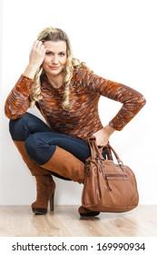 sitting woman wearing fashionable brown boots holding a handbag