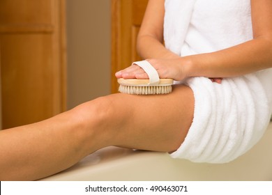 Sitting woman's arm holding dry brush to top of outstretched leg