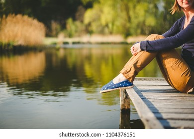 Sitting Woman's feet in a sneakers near the lake