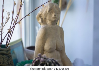 The sitting wood sculpture of a  woman