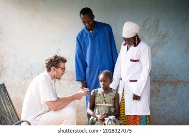Sitting young caucasian volunteer doctor is explaining a suspicious little African girl how the instrument is working he is using on her to check her respiratory functions