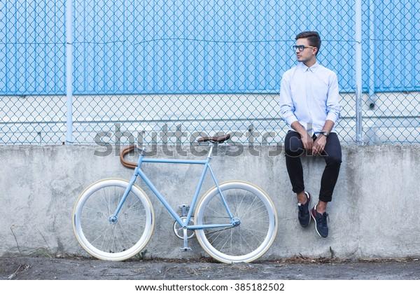 Sitzen junger Hipster und trendiges City-Rad