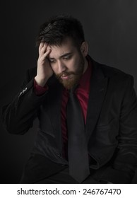 Sitting Young Man in Black and Maroon Formal Attire Suffering Headache with Hand on his Head. Captured on Gray Background