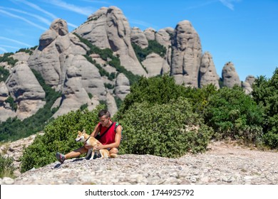 A sitting young man and his dog at the top of Montserrat mountain, Barcelona