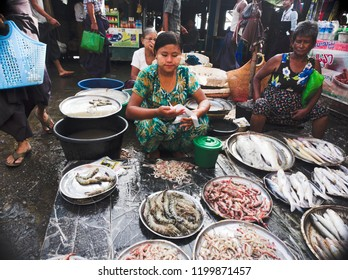 Sittwe Myanmar on December 19, 2015: a lady was selling fishes and prawns in the market