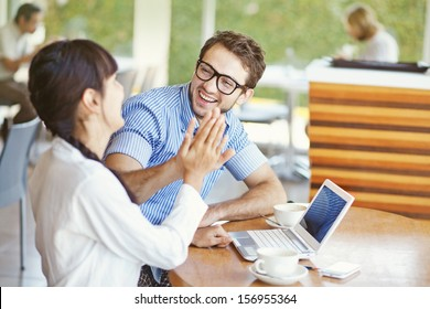 situation in office - two workers giving high five