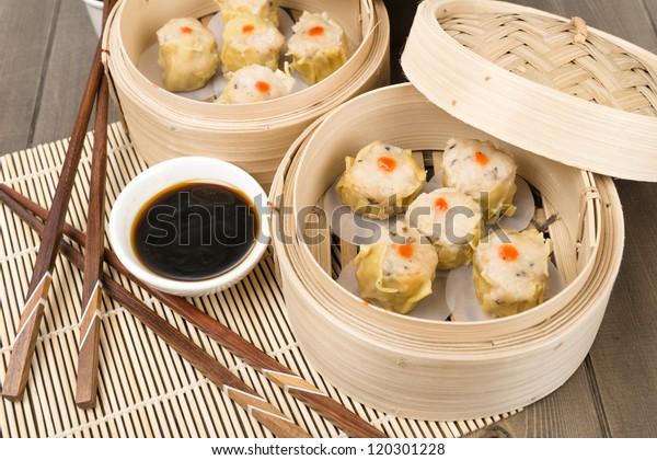 Siu Mai - Chinese steamed pork dumplings in bamboo steamers. Dim Sum