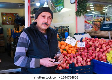 Sivas/Turkey 20 March 2019:Greengrocer drinking tea and thinking about the sales. Fresh vegetables and friuts in traditional local market. Local fruiterer selling fruit in Sivas. Farmer's Market Stall