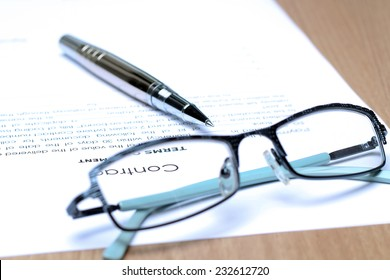 Siver Pen on the contract papers, glasses above