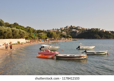 Sivota, Greece - September 3rd 2018: Tourists and locals enjoying the warm coastal waters at the town beach near the harbor in Sivota, Greece.