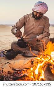 SIWA, EGYPT - April 2018: Bedouin tea on the fire in Sahara desert, Egypt. Bedouin man wearing traditional turban preparing tea, Siwa, Egypt