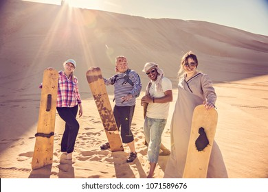 SIWA, EGYPT - April 2018: Group of happy young people with sand boards in Sahara desert, Siwa oasis, Egypt