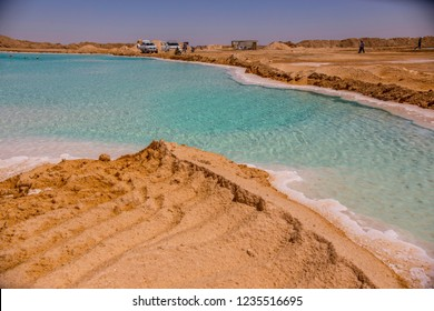 SIWA, EGYPT - April 2018: Jeep cars on the bank of Salt lake with turquoise water and white salt on the shore near Siwa oasis, Egypt