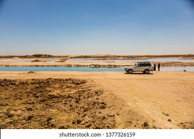 SIWA, EGYPT - April 2018: Jeep car on the bank of Salt lake with turquoise water and white salt on the shore near Siwa oasis, Egypt