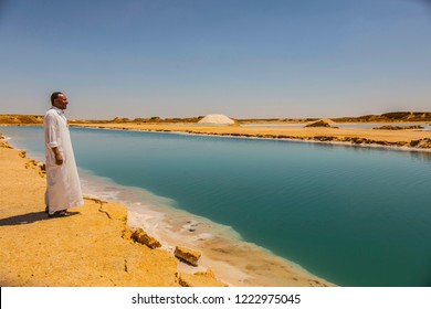 SIWA, EGYPT - April 2018: Man dressed in Arabic clothes near Salt lake with turquoise water and white salt on the shore near Siwa oasis, Egypt