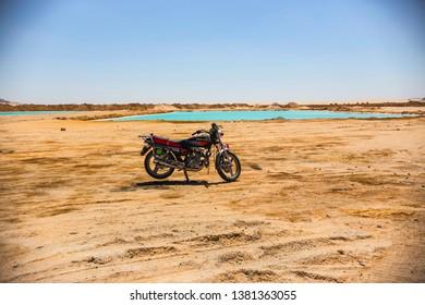 SIWA, EGYPT - April 2018: Motorcycle on the bank of Siwa lake in Egypt