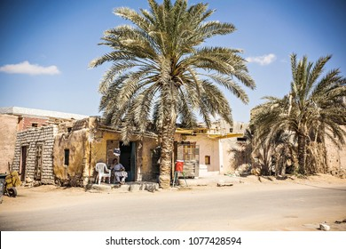 SIWA, EGYPT - April 2018: Siwa oasis, road in the desert, Egyptian man sitting near the house under the palm tree, Siwa, Egypt