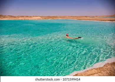 SIWA, EGYPT - April 2018: Young woman swimming in salt lake at Siwa oasis, Egypt