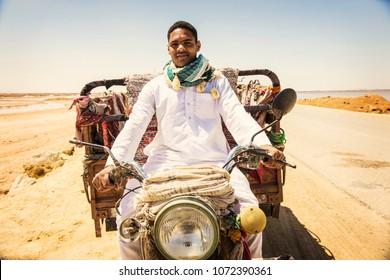 SIWA, EGYPT - April 2018: Young Egyptian man wearing Bedouin clothes driving traditional tuk-tuk (bajaj) at Siwa oasis, Egypt