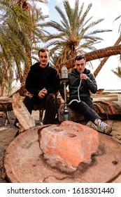 Siwa Oasis, Egypt Jan 10, 2020 Two men smoke a shisha pipe near a campfire.