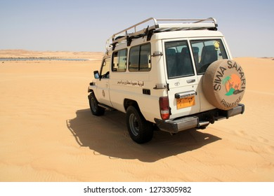 Siwa Oasis, Egypt - September 25th 2009: Rear view of an off-road vehicle standing on top of a sand dune ready to go towards the distant desert oasis