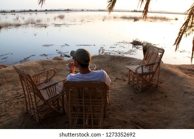 Siwa Oasis, Egypt - September 28th 2009: Man with cap sitting on a chair at the water's edge on Fatnas Island, an island at Siwa Oasis in the Egyptian Sahara Desert, and enjoys a beautiful sunset