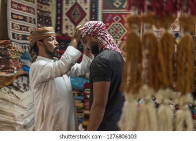 Siwa/Egypt - 03/16/2018: Portrait of a bedouin Arabic man helping another with wearing a head scarf bedouin style in Siwa Egypt