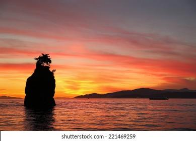 Siwash Rock Sunset, English Bay, Vancouver. Sunset over English Bay silhouetting Siwash Rock in Stanley Park. Vancouver, British Columbia, Canada.