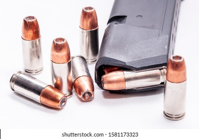 Six 9mm hollow point bullets next to a loaded pistol magazine on a white background