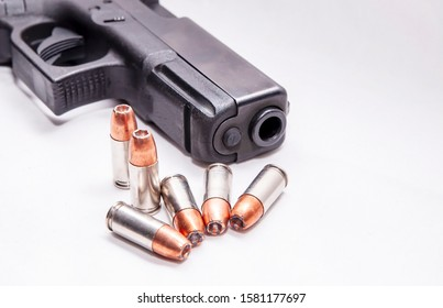 Six 9mm hollow point bullets in front of a black 9mm pistol on a white background