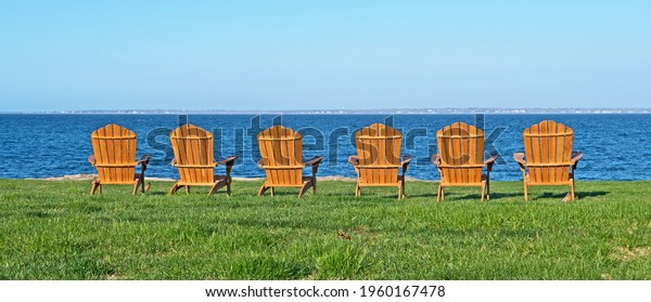Six adirondack style chairs are set on a lawn and facing Buzzard's Bay in Fairhaven, Massachusetts.