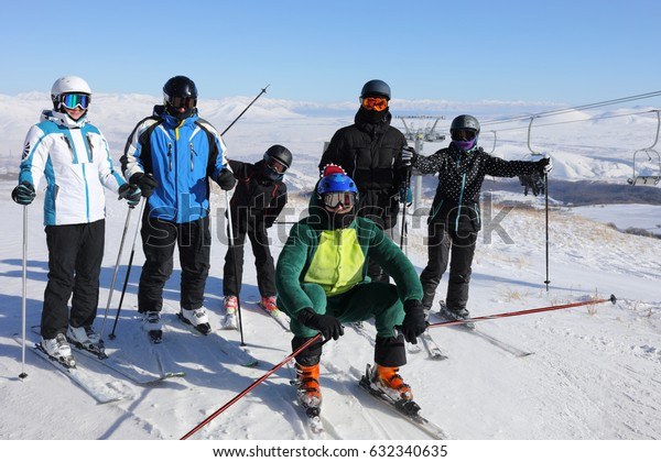 Six adults and children in ski goggles are on mountain with cableway in ski resort at winter day